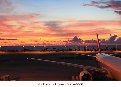 Colorful of sunset in the airport with aeroplane wing, as nature background or print card. Business and transportation concept.