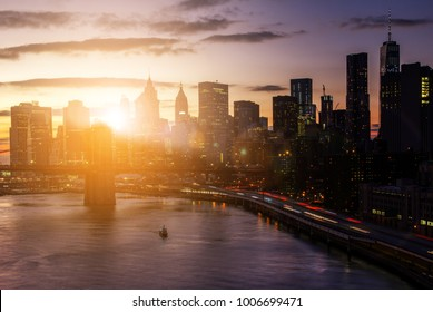 Colorful sunset behind the Brooklyn Bridge and skyscrapers of the Manhattan skyline in New York City