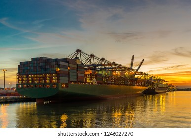 Colorful sunset at Burchardkai behind a container ship in the port of Hamburg