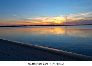 A colorful sunset colors the horizon beyond a dark beach and inlet shore in North Carolina, USA
