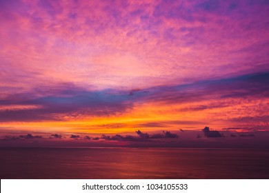Colorful sunset with dramatic of purple , magenta and orange cloudy sky in evening over an ocean.One of most beautiful sunset view point at Leam Promthep Cape, Phuket, Thailand.