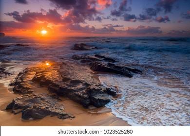 Colorful sunset with dramatic sky at Amoreira beach near Aljesur, Portugal.