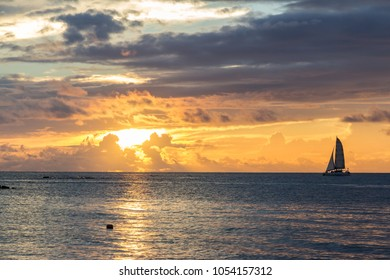 Colorful sunset dusk scene on a Mauritius island beach at the Indian Ocean with a sailboat crossing the horizon