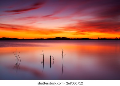 Colorful sunset at Gossan reservoir, Riotinto, Huelva, with reflections and symmetries