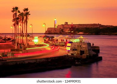 Colorful sunset in Havana with a view of the bay and the light in the lighthouse of El Morro