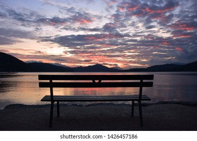 A colorful sunset at lake worth with an empty bench in the foreground. carinthia, kärnten