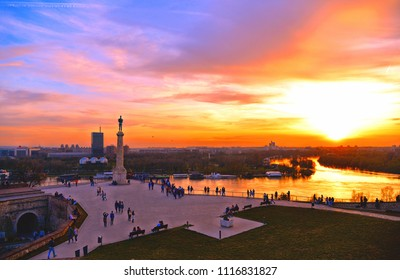 Colorful Sunset light and clouds on Danube river, statue and silhouettes of people in fortress Kalemegdan in Belgrade Serbia