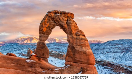 A colorful sunset lights up the La Sal Mountains behind iconic Delicate Arch in after a Febraury 2019 snowstorm in Arches National Park, Moab, Utah.