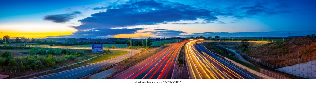 Colorful sunset at M1 motorway near Flitwick junction with cars light trails. United Kingdom
