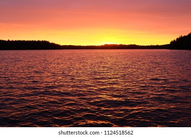 Colorful sunset at midsummer night. Clouds reflecting on lake.  Lakeview, Finland.