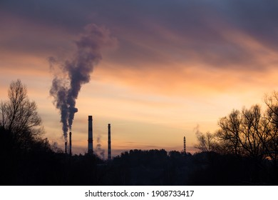 Colorful sunset on the background of smoking pipes. Industrial landscape at dusk