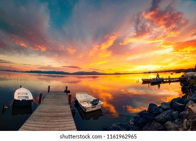 Colorful sunset on the fisherman lagoon with perfect calm water and reflection. Wooden pier on the lagoon at sunset, perfect reflections.