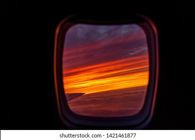 Colorful Sunset out of plane window jet air travel sun purple and orange