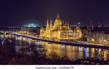 Colorful sunset over Budapest. Wonderful evening cityscape. Night view of the illuminated building of the Hungarian parliament over Danube river with reflected. Popular touristic locations