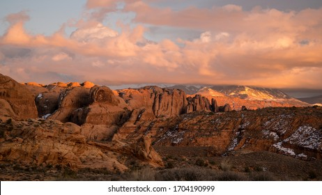 Colorful sunset over desert rocky fin layers in Moab looking towards the La Sal Mountains with colorful clouds.