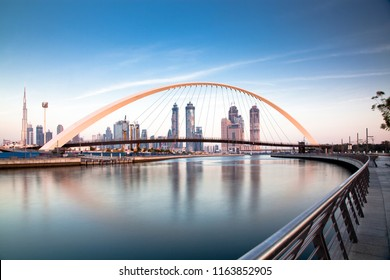 colorful sunset over Dubai Downtown skyscrapers and the newly built Tolerance bridge as viewed from the Dubai water canal.