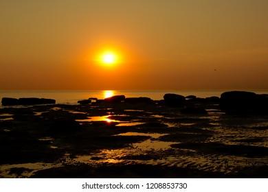 Colorful sunset over the North sea with rocks in the water along the opal coast in Nord Pas de Calais region, France
