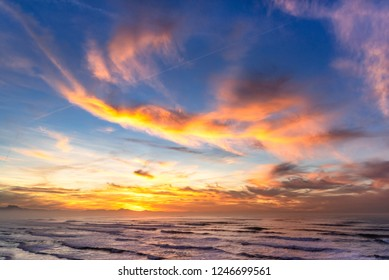 Colorful sunset over the ocean with shiny clouds. Biarritz, Basque country of France.