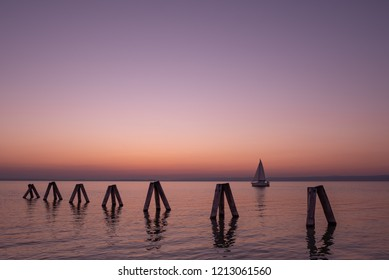 Colorful sunset with pier over lake Neusiedler in Podersdorf am See, Austria, Burgenland
