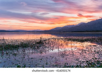 Colorful sunset reflected in the lake with the mountains at the background