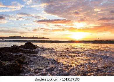 Colorful sunset reflecting on the waves and wet sand with a grouping of rocks in the bottom of the frame in Playa Flamingo, Costa Rica