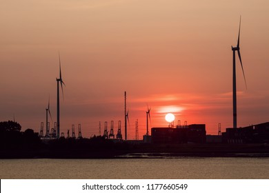 Colorful sunset at a riverbank with the silhouette of Port of Antwerp on the background.