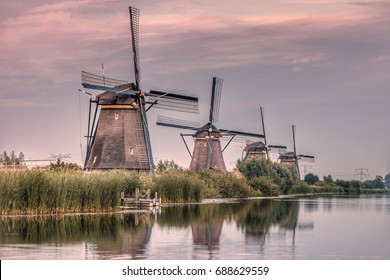 Colorful sunset sky by the Famous Dutch wooden Windmills Kinderdijk Holland. Sunny summer evening at the windmill village countryside.Netherlands,UNESCO World Heritage Site.Kinderdijk Windmill village