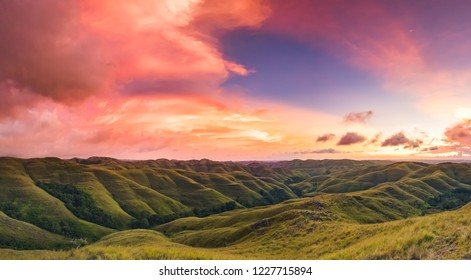 Colorful sunset sky over mountain panorama, Merdeka Hill, Bukit Wairinding, East Sumba, Indonesia. Bright pink, blue, green colors. Travel Background. Nature landscape. Untouched wild island