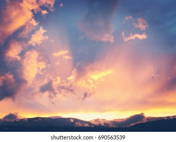 Colorful sunset sky over mountains.  Colorful clouds and sun rays.