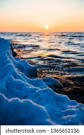 Colorful sunset. Snow-covered seacoast on a sunny winter day. Cold waves over the Baltic sea, Latvia