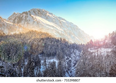 Colorful sunset in snowy winter mountains and woodland. Hintersteiner Tal, Allgau, Bavaria, Germany.
