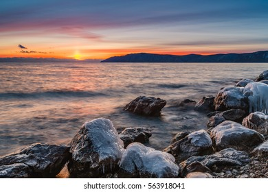 Colorful sunset with stones frozen winter lake