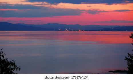 Colorful Sunset Summer View. Beautiful sea and sky reflection with dramatic clouds over the sea and mountain range in backgrounds clouds reflecting on surface of water
