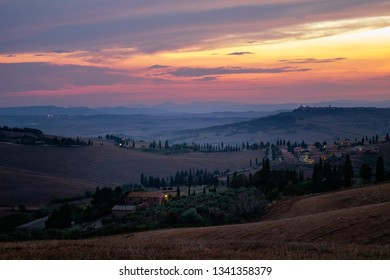 Colorful sunset in Tuscany. Wonderful artistic Tuscan landscape with cypresses, wavy fields and vivid sky, Italy
