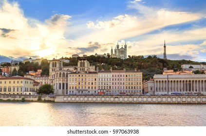 Colorful sunset at Vieux Lyon and Fourviere Basilica seen from the riverbank of the Saone in Lyon.