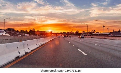Colorful sunset while driving on a freeway in South San Francisco bay area, California