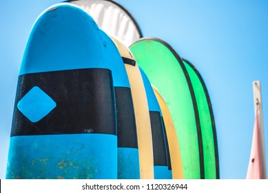 Colorful Surfboard noses on a sunny day at the beach in Tamraght, Morocco. Soft boards and beachflags for beginners.