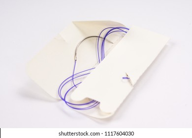 Colorful surgical nylon monofilament suture with curved needle isolated on an abstract blurred white background. Healthcare, medical and surgery concept. Detailed close up with soft selective focus
