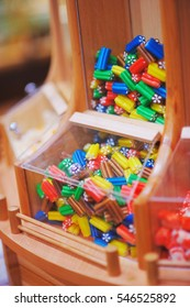 Colorful sweet jelly candies in a glass box on wooden shelves of the store
