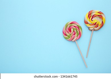 Colorful sweet lollipops on blue background