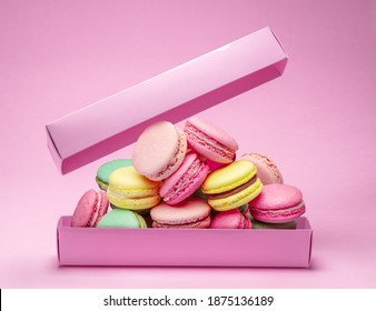 Colorful sweet macarons or macaroons, flavored cookies are in the paper box on the pink background.