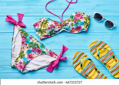 Colorful swimsuit, glasses, sandals. Bathing female suit and beach accessories.