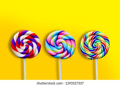 Colorful swirl lollypops over yellow background