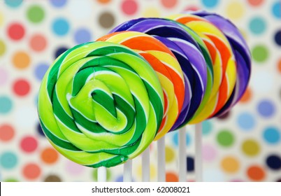 Colorful swirled lollipops on a party background