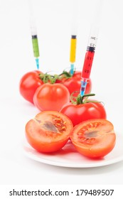 Colorful syringes sticking out of tomatoes