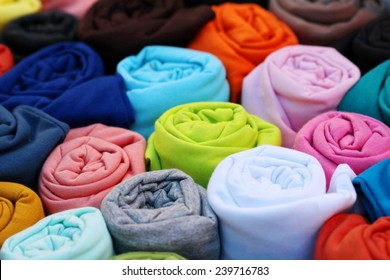 colorful t shirt cotton fabric roll laundry , many reels of threads for embroidery colorful background