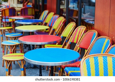 Colorful tables and chairs of empty outdoor cafe in Paris, France