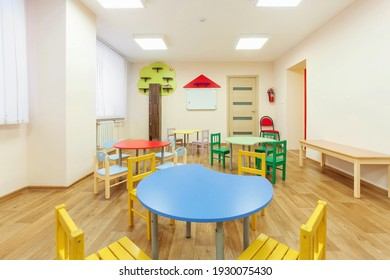 Colorful tables for classes for children and light beige colored game room in the kindergarten.