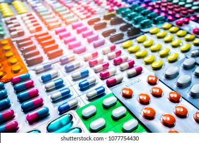 Colorful of tablets and capsules pill in blister packaging arranged with beautiful pattern with flare light. Pharmaceutical industry concept. Pharmacy drugstore. Antibiotic drug resistance.
