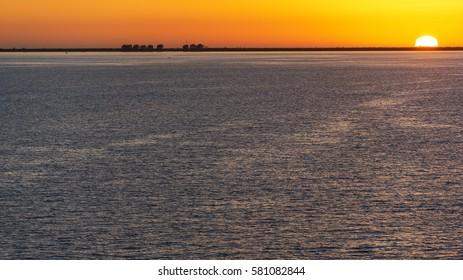 Colorful Tampa Bay sunset with sun halfway set below the horizon